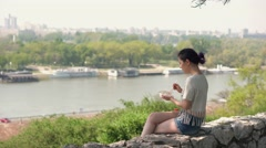 Pretty woman eating salad on lunch break in City Park - stock footage