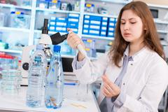 woman assistant in laboratory with multi pipette in the clinic, the research  - stock photo