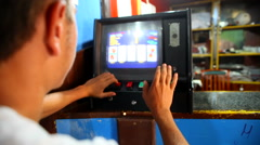 Guy playing cart on the old video poker machines in the bar rn Stock Footage