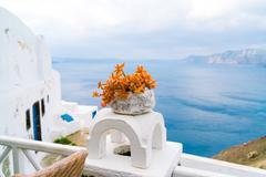 White villa house in Oia with stairs and a flower pot, Santorini - stock photo