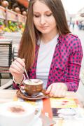 Woman drinking cappuccino at an outdoor cafe - stock photo