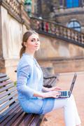 Girl works on laptop sitting on a bench in the park Stock Photos