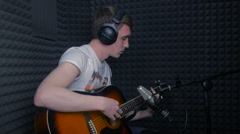 Man playing guitar, recording a song in professional sound studio - stock footage