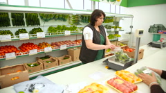 Seller in the store weigh cucumbers Stock Footage