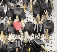 Black car keys and a red one on a special  wall Stock Photos