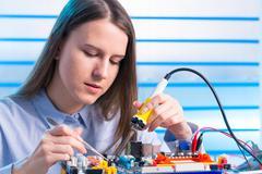 Young woman technician repair electronics device Kuvituskuvat