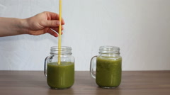 Green smoothies in mason jars with tubes on a wooden table Stock Footage