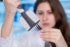 Woman technician with multipipette in genetic laboratory Stock Photos