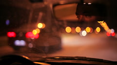 Man driving a car in the city at night Stock Footage