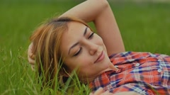 Girl sexy lying on green grass outdoors slow motion Stock Footage