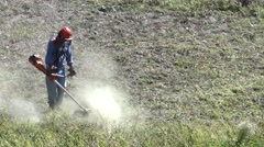 Worker who cleans with the cutter gasoline, a land filled with weeds, located Stock Footage