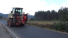 Tractor heavy going on a paved country road among fields uncultivated Stock Footage