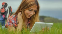 girl sexy with tablet lying on green grass slow motion outdoors - stock footage
