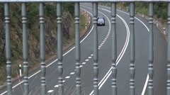 Car traffic on a paved road seen through rail mounted above a bridge Stock Footage