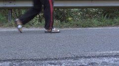 Feet of a pilgrim who goes on an asphalt road bordered by rail, on the Camino Stock Footage