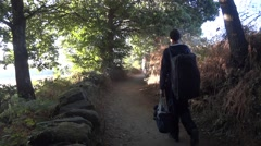 Pilgrims carrying two heavy bags go on a trail through the woods on the Camino Stock Footage