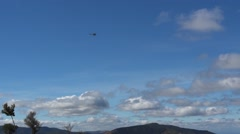 Military helicopter flying against a blue sky with fluffy clouds and gray Stock Footage