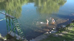 Minor children who play in the shallow water of a river from ses Stock Footage