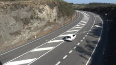 Passenger car speeding on a road with four lanes with a curve to the left Stock Footage