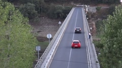 Cars crossing a concrete bridge while some pedestrians are leaning against the Stock Footage