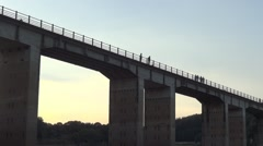 Groups of people walking on a tall bridge built over a deep valley Stock Footage