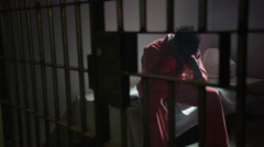 People in Jail for Crimes - Sad African American Man on bed in cell - stock footage