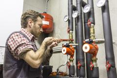 plumber at work installing a circulation pump - stock photo