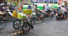 Heavy motorcycle traffic passing street vendor's food cart in Ho Chi Minh Cit Stock Footage