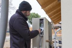 Plumber at work installing a heat pump Stock Photos