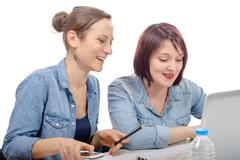 two women college working on  laptop computer - stock photo