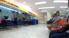 People seated in queue in a utility service center office Stock Footage