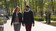 Loving couple walking along park alley Stock Footage