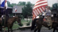 1955: Horse riding cowboys carry flags while folks watch the rodeo. - stock footage