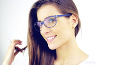 Cute young woman with glasses playing with hair blinking to camera 4k isolate Stock Footage