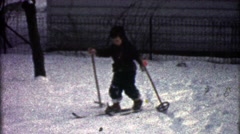 1954: Boy practicing winter cross country snow skiing in backyard. - stock footage