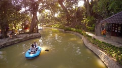 Tourists in rubber raft, drifting along on river at base of Prenn Waterfall Stock Footage