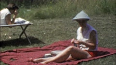 1954: Woman sunbathing on cut grass lawn in funny Asian style hat. Stock Footage