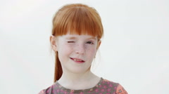 Little redheaded girl is  winking, white background, close up - stock footage