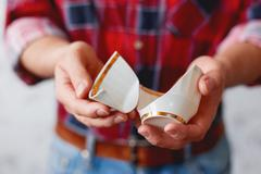Man in plaid tartan shirt holds a broken white cup. Damaged mug with golden d - stock photo