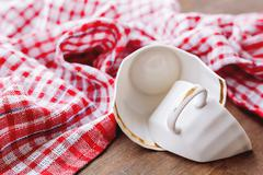 Broken white cup on wooden background with plaid red towel. Damaged mug with Stock Photos