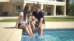 young couple sitting at poolside, big house in background - stock footage