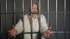 Woman excitedly reaching through prison bars Stock Footage