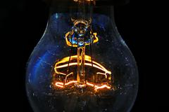 Old light bulb glowing in dark - stock photo