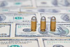 Bullets on dollar bills - stock photo