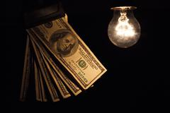 Hanging light bulb dangle on a wire illuminating bank notes - stock photo