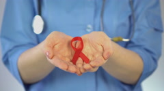 Female gynecologist in blue coat holding red ribbon in palms, AIDS awareness - stock footage