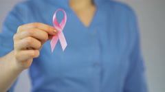 Female physician attaching pink ribbon to coat, breast cancer awareness campaign Stock Footage