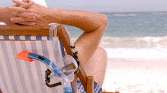 A mature man is sitting on a deck chair Stock Footage