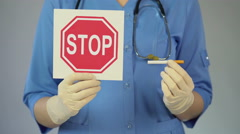 Hospital nurse holding stop sign and a cigarette, preventing unhealthy lifestyle Stock Footage