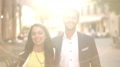 Beautiful young couple walking in bright sunshine Stock Footage